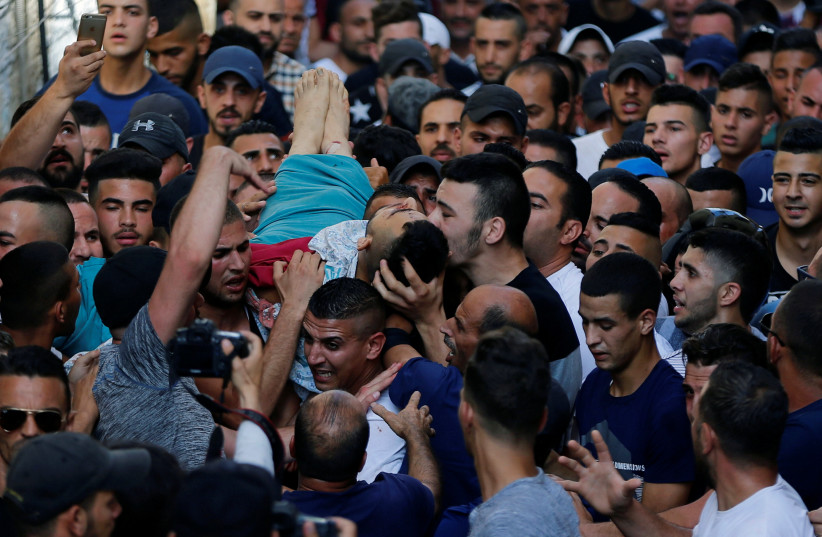 A mourner kisses the body of Palestinian Mohammad Abu Ghannam during his funeral in the east Jerusalem neighbourhood of A-tur July 21, 2017. (photo credit: AMMAR AWAD/REUTERS)