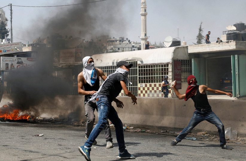 Palestinian protesters hurl stones towards Israeli troops during clashes near Qalandiya checkpoint near the West Bank city of Ramallah (photo credit: REUTERS/MOHAMAD TOROKMAN)