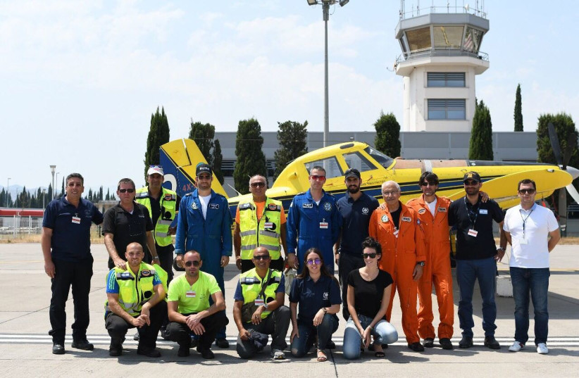 The Israeli delegation of firefighters pose in front of a plane in Montenegro. (photo credit: POLICE SPOKESPERSON'S UNIT)