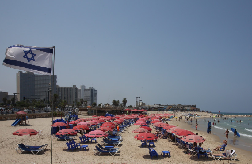 Israeli flag waving at a Tel Aviv beach. (photo credit: MARC ISRAEL SELLEM)