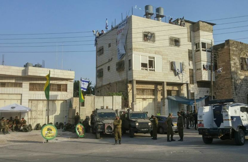 IDF soldiers outside of Beit Hamachpela building in Hebron.  (photo credit: ENLARGE THE PLACE OF THY TENT)