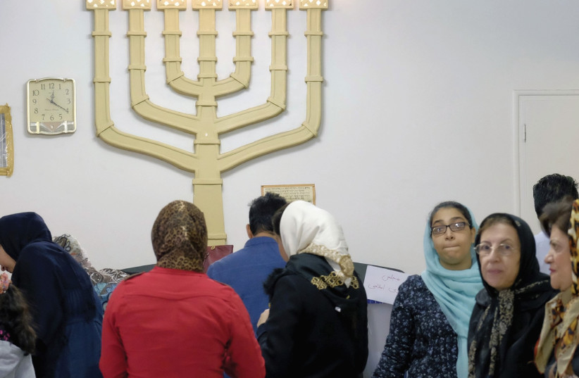 Iranian Jews gather at a synagogue, used as a polling station, during parliamentary elections in 2016 (photo credit: REUTERS)