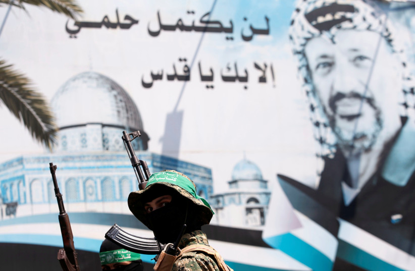 A poster depicting late Palestinian leader Yasser Arafat is seen as Hamas militants take part in a protest against Israel's new security measures at the entrance to the al-Aksa mosque (Temple Mount) compound, in Gaza City July 21, 2017.  (photo credit: REUTERS)
