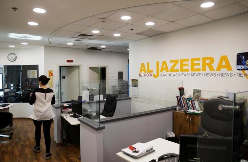 An employee walks inside an office of Qatar-based Al-Jazeera network in Jerusalem June 13, 2017.  (photo credit: REUTERS)
