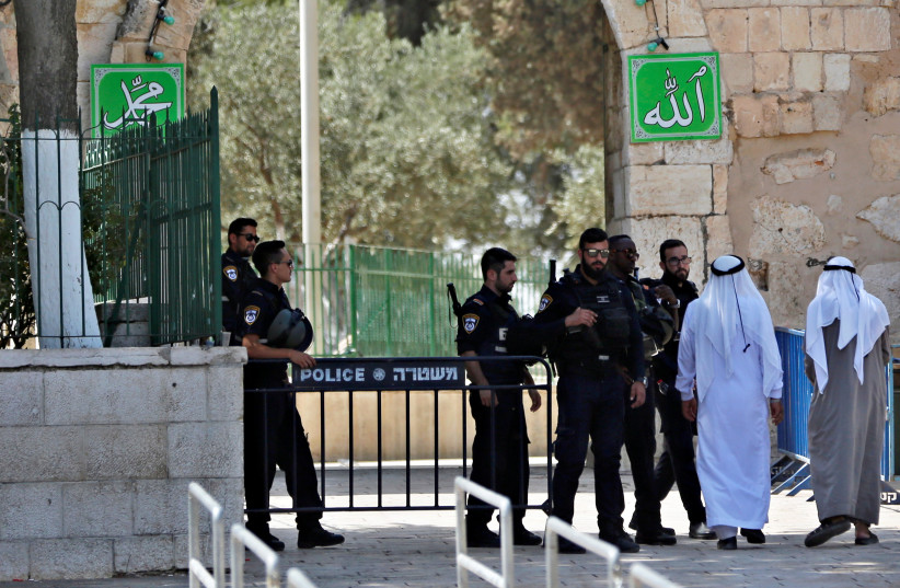 Palestinians walk next to Israeli security forces at the entrance of the compound known to Muslims as Noble Sanctuary and to Jews as Temple Mount at morning after Israel removed the new security measures there, in Jerusalem's Old City (photo credit: RONEN ZVULUN/REUTERS)