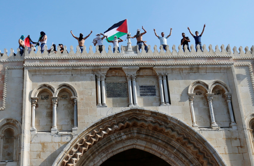 A Palestinian flag is waved at the Temple Mount in Jerusalem's Old City (photo credit: MUAMMAR AWAD/REUTERS)