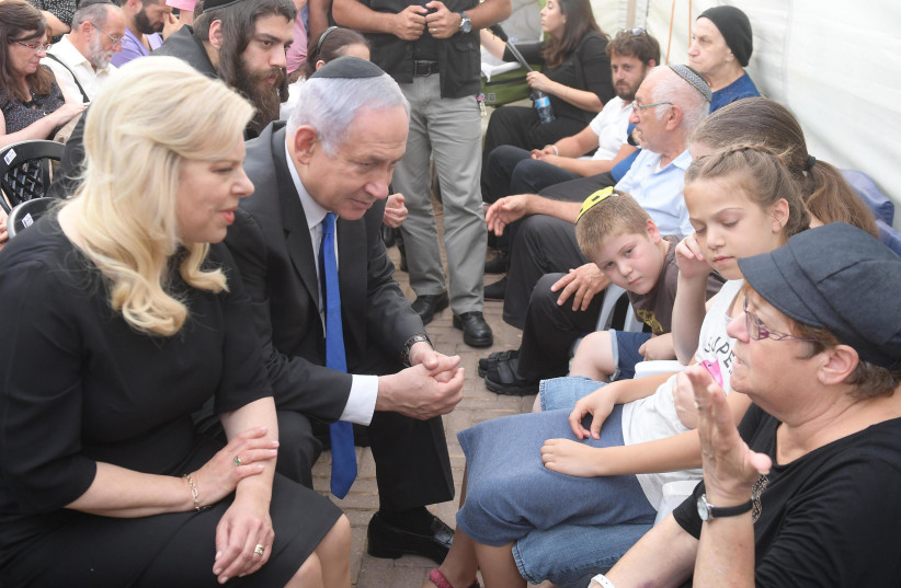 Israeli Prime Minister Benjamin Netanyahu speaks to the family members of the three people killed by a Palestinian terrorist in Halamish (photo credit: AMOS BEN-GERSHOM/GPO)