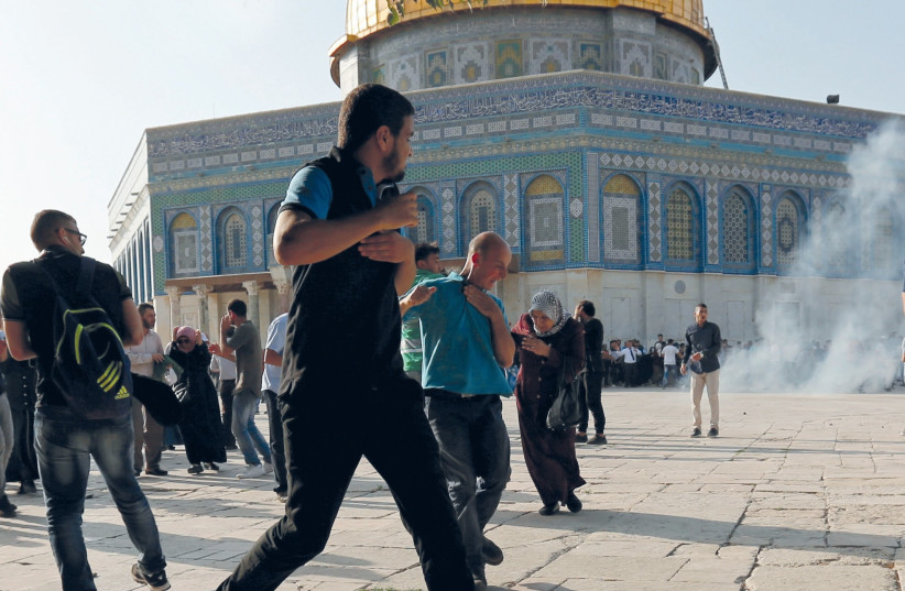 MUSLIM RIOTERS run as security personnel disperse them on the Temple Mount yesterday (photo credit: REUTERS)