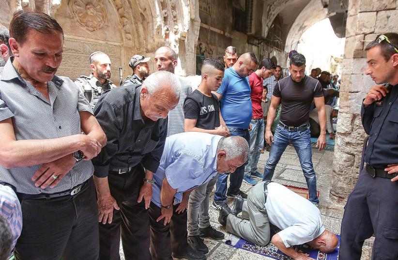 MUSLIMS BOYCOTTING the al-Aksa compound to protest metal detectors, even after they were dismantled, pray in Jerusalem's Old City. (photo credit: MARC ISRAEL SELLEM/THE JERUSALEM POST)