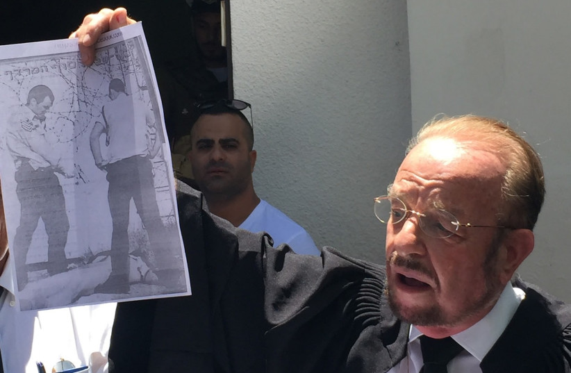Elor Azaria's attorney Sheftel holding up a sign of a similar incident which took place in 2002, July 30, 2017. (photo credit: ANNA AHRONHEIM)