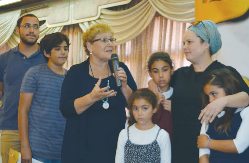MIRIAM PERETZ, the mother of fallen Golani Brigade soldiers Uriel and Eliraz, speaks at the Colel Chabad ceremony yesterday, surrounded by her family. (photo credit: KAYLA STEINBERG)