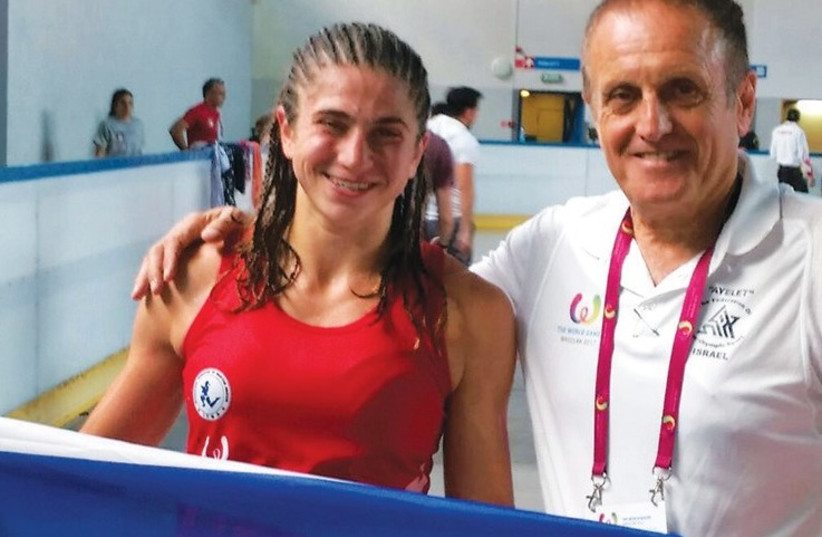 Muaythai fighter Nili Block (left) poses with the Israel flag alongside Dr. Itzik Ben- Melech, who is in charge of Ayelet's professional department, after winning a bronze medal in the closing day of competition at the World Games yesterday (photo credit: Courtesy)