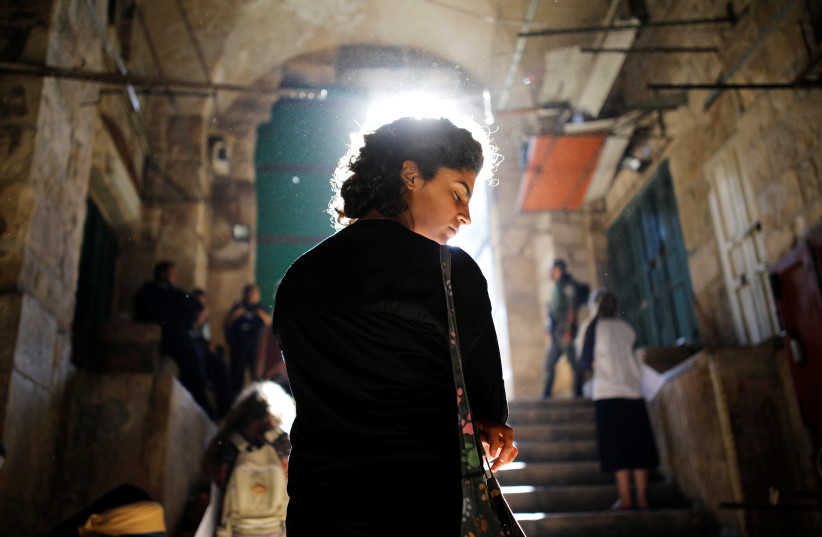 A Jewish worshipper prays in front of an entrance to the compound known to Muslims as Noble Sanctuary and to Jews as Temple Mount, on Tisha B'Av, a day of fasting and lament, in Jerusalem's Old City August 1, 2017.  (photo credit: REUTERS/AMIR COHEN)