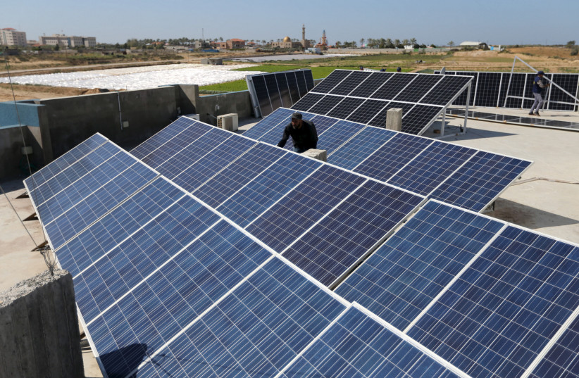 A worker installs solar panels on a roof in Gaza City (photo credit: IBRAHEEM ABU MUSTAFA / REUTERS)