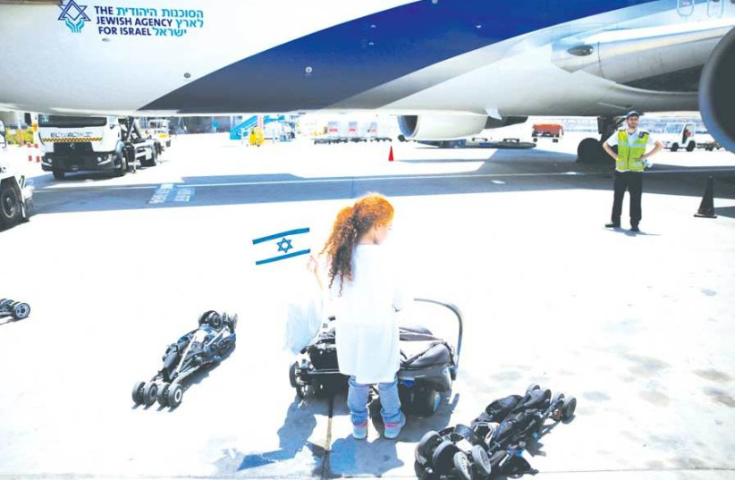 A YOUNG olah, newly arrived from France, waves an Israeli flag after disembarking from a plane upon arriving in Israel on a special flight organized by the Jewish Agency at Ben-Gurion Airport, last year. (photo credit: RONEN ZVULUN / REUTERS)