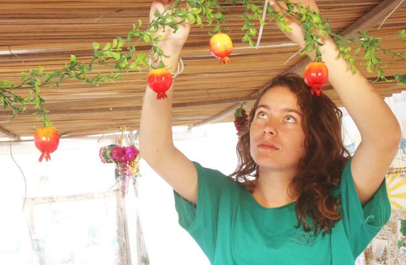 A WOMAN decorates her sukka ahead of the holiday.  (photo credit: MARC ISRAEL SELLEM)