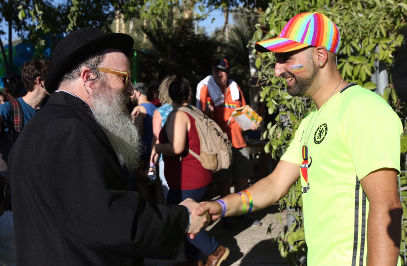 Jerusalem Gay Pride Parade participant shakes hands with a religious Jewish man (photo credit: MARC ISRAEL SELLEM)