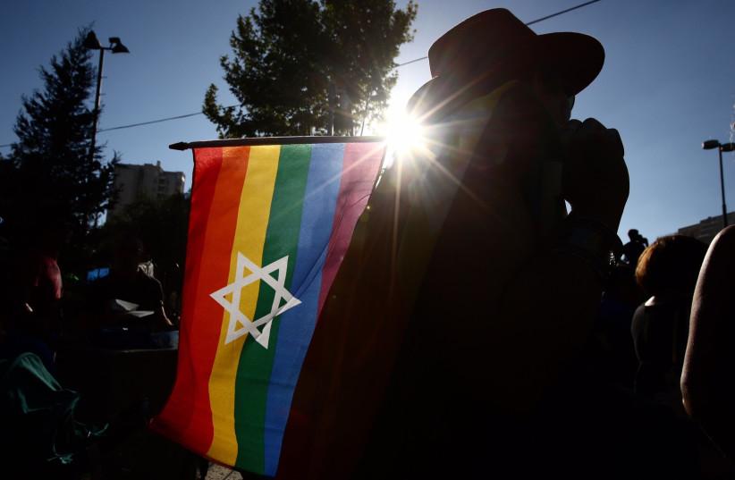 Man holds a Star of David rainbow flag at the 2017 Jerusalem Gay Pride Parade (photo credit: MARC ISRAEL SELLEM)