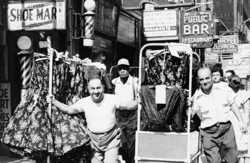 Men pulling racks of clothing on busy sidewalk in Garment District, New York City, 1955 (photo credit: PUBLIC DOMAIN / AL RAVENNA - WORLD TELEGRAM STAFF PHOTOGRAPHER)
