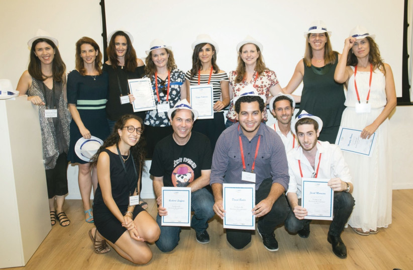 Newly minted graduates of TheNest's second cohort of small-business owners pose with their certificates of completion and graduation caps at Wix headquarters in the Tel Aviv Port (photo credit: SASHA PRILUTSKY/DVISION)
