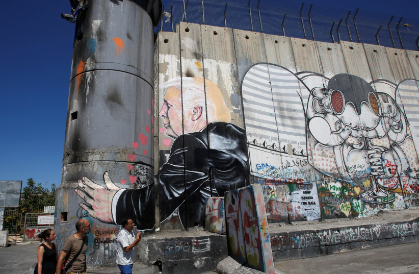 Tourists stand in front of a grafitti depicting US President Donald Trump on the controversial Israeli barrier in the West Bank town of Bethlehem August 4, 2017.  (photo credit: REUTERS)