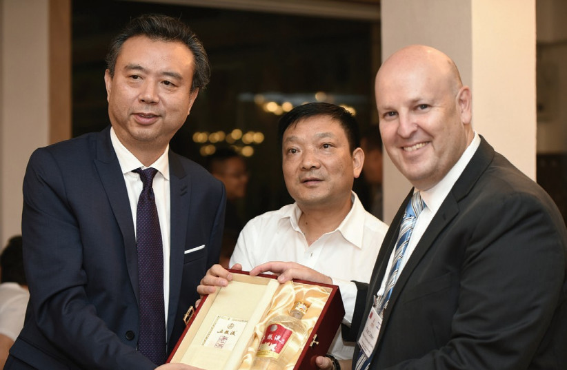 FROM LEFT, the chairman of Wuliangye, Li Shuguang; the mayor of Yibin, Du Ziping; and Ohad Cohen, trade commissioner and director of Israel's Foreign Trade Administration in the Ministry of Economy and Industry. (photo credit: AVI HAYOUN)