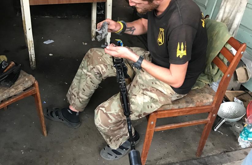 A Ukraine Donbass volunteer cleans his rifle, Summer 2017. (photo credit: SETH J. FRANTZMAN)
