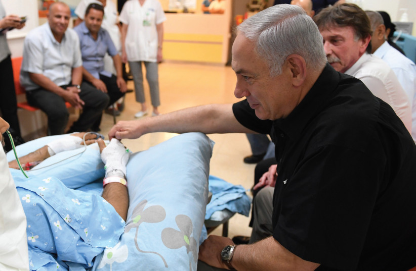 Prime Minister Benjamin Netanyahu visits Niv Nehemiah yesterday at Kaplan Medical Center in Rehovot. Nehemiah was stabbed last week by a terrorist at a supermarket in Yavne. (photo credit: KOBI GIDEON/GPO)