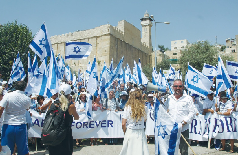 PARTICIPANTS IN the annual Hebron march show the flag, with the Tomb of the Patriarchs in the background (photo credit: TOVAH LAZAROFF)