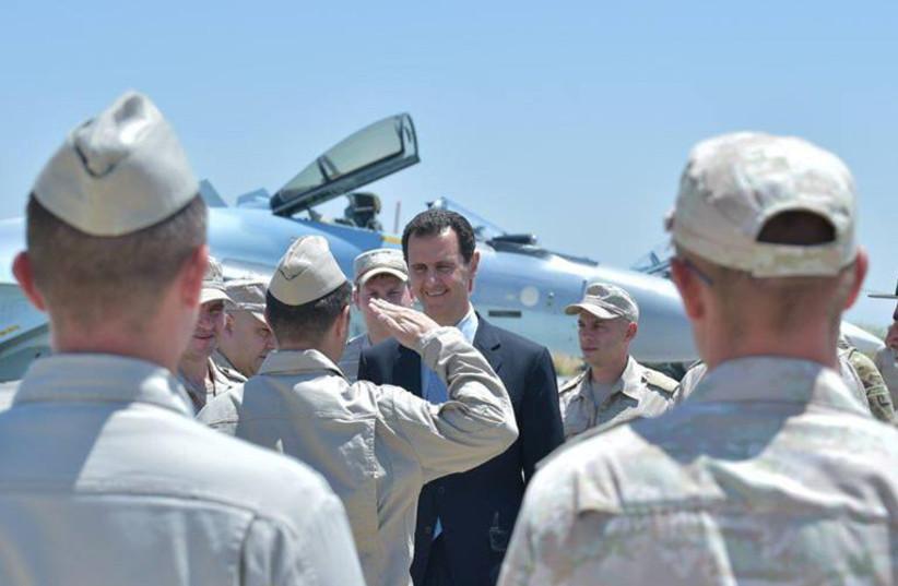 Syria's President Bashar al-Assad visits a Russian air base at Hmeymim, in western Syria (photo credit: SANA/REUTERS)