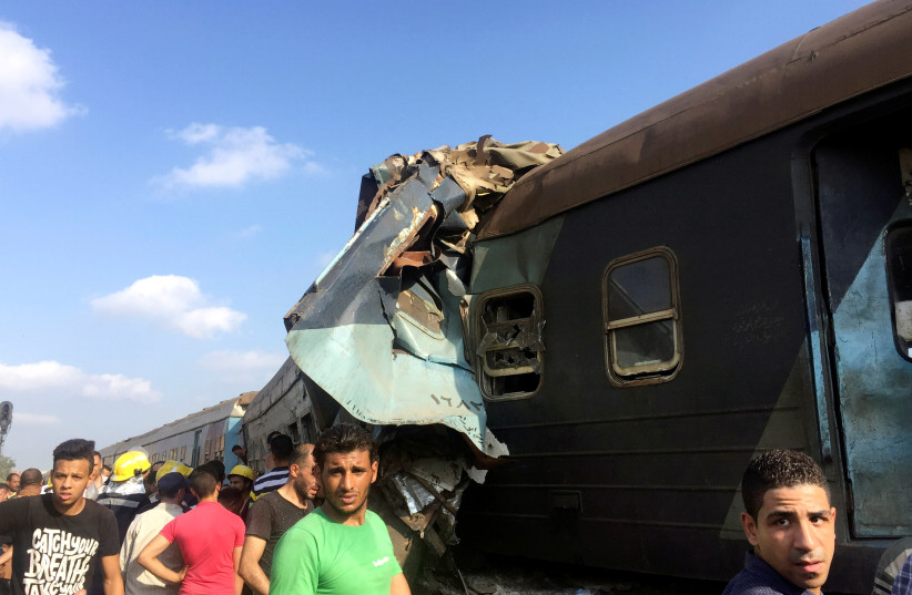 Egyptians look at the crash of two trains that collided near the Khorshid station in Egypt's coastal city of Alexandria, Egypt August 11, 2017 (photo credit: REUTERS/OSAMA NAGEB)