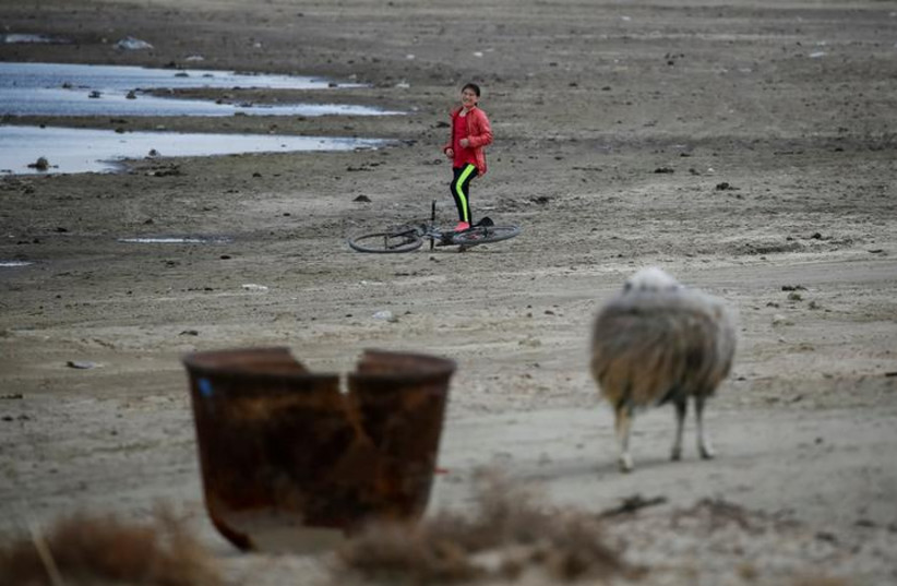 A girl smiles next to her bicycle at the old part of the village of Karateren, near the Aral Sea, south-western Kazakhstan, April 15, 2017.  (photo credit: REUTERS/SHAMIL ZHUMATOV)