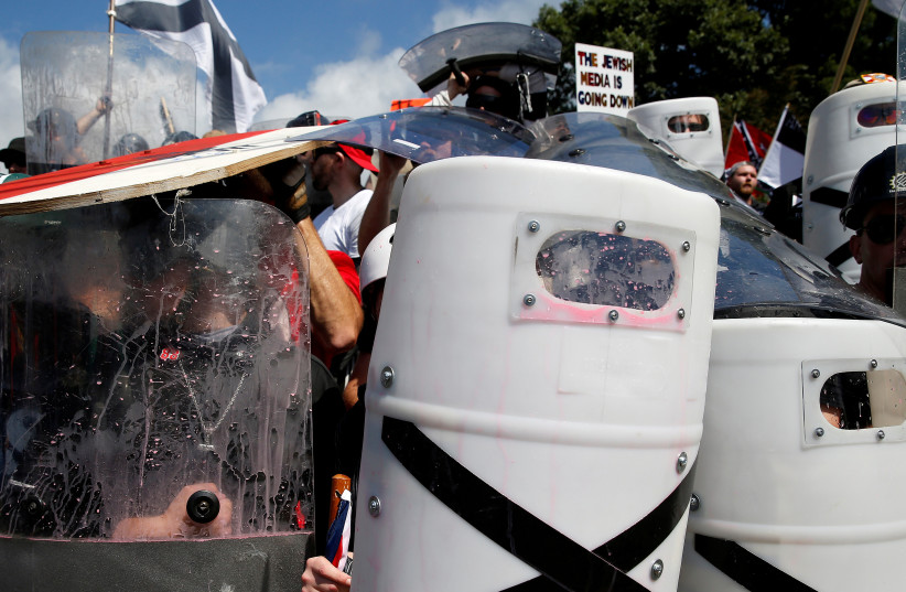White supremacists shelter behind their shields after clashing with counter protesters at a rally in Charlottesville, Virginia, US, August 12, 2017. (photo credit: REUTERS/JOSHUA ROBERTS)