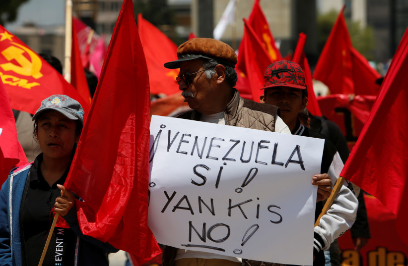 """A man holds up a placard during a protest of civil organizations in support of Venezuelan President Nicolas Maduro's government, in Mexico City, Mexico August 12, 2017. The Placard reads: """" ! Yes to Venezuela! and Not, Yankee! """". (photo credit: GINNETTE RIQUELME/ REUTERS)"""