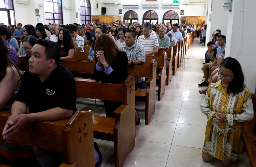 Local residents pray during a Sunday mass at Sta Barbara Church on the island of Guam, a US Pacific Territory, August 13, 2017. (photo credit: ERIC DE CASTRO/ REUTERS)