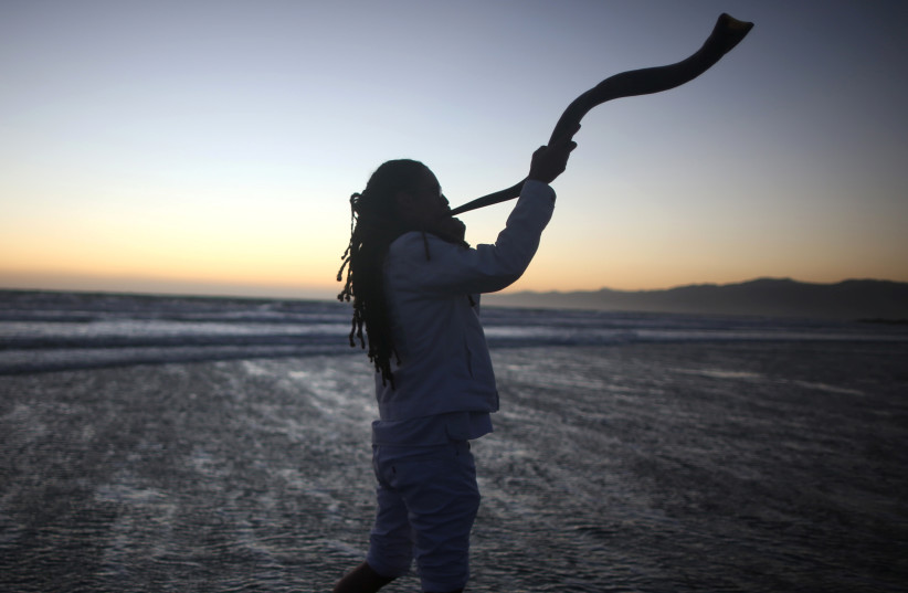 A young man plays the shofar during the Nashuva Spiritual Community Jewish New Year celebration  (photo credit: LUCY NICHOLSON / REUTERS)