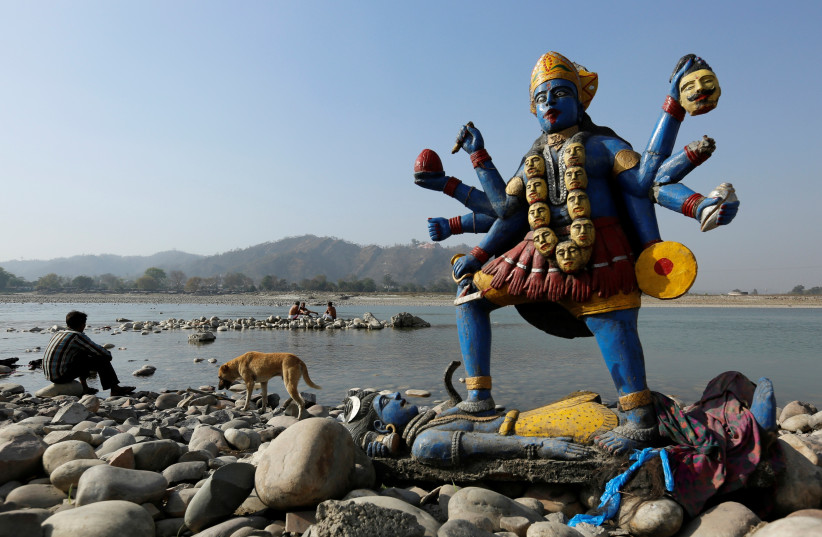 A man sits next to a damaged idol of Hindu goddess Kali which was taken out after its immersion in the river Ganges in Haridwar, India, March 29, 2017.  (photo credit: DANISH SIDDIQUI/ REUTERS)