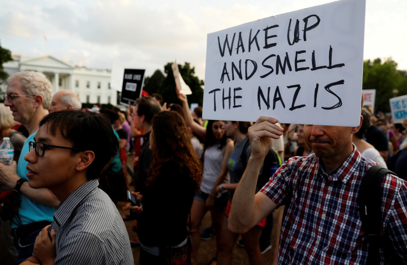 """People gather for a vigil in response to the death of a counter-demonstrator at the """"Unite the Right"""" rally in Charlottesville, outside the White House in Washington, U.S. August 13, 2017.  (photo credit: JONATHAN ERNST / REUTERS)"""