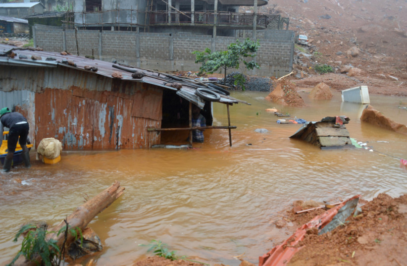 Residents save belongings in floodwaters after a mudslide in the mountain town of Regent, Sierra Leone August 14, 2017.  (photo credit: ERNEST HENRY / REUTERS)