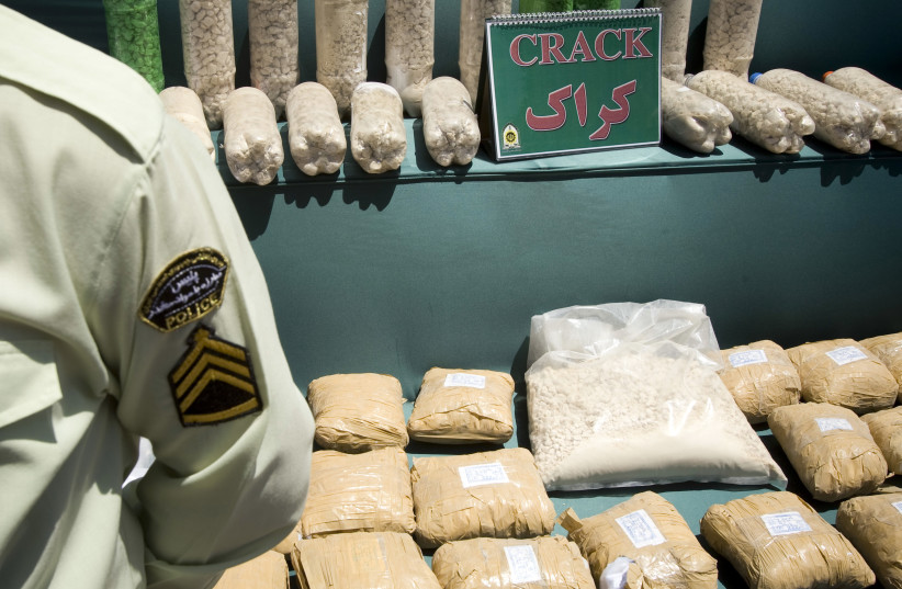 An Iranian anti-narcotics policeman stands guard beside a display of confiscated drugs (photo credit: CAREN FIROUZ / REUTERS)