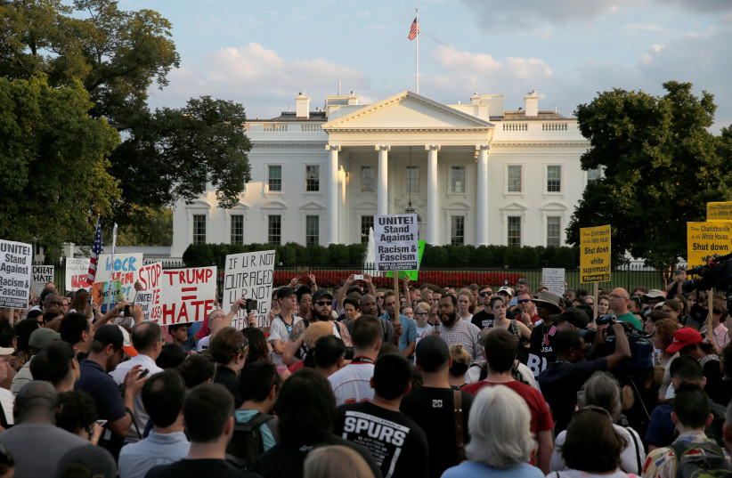 """People gather for a vigil in response to the death of a counter-demonstrator at the """"Unite the Right"""" rally in Charlottesville, outside the White House in Washington, U.S. August 13, 2017.  (photo credit: REUTERS / JONATHAN ERNST)"""
