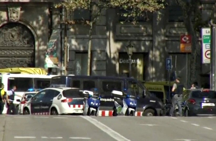 A still image from video shows a police cordon on a street in Barcelona, Spain following a van ramming (photo credit: REUTERS TV)