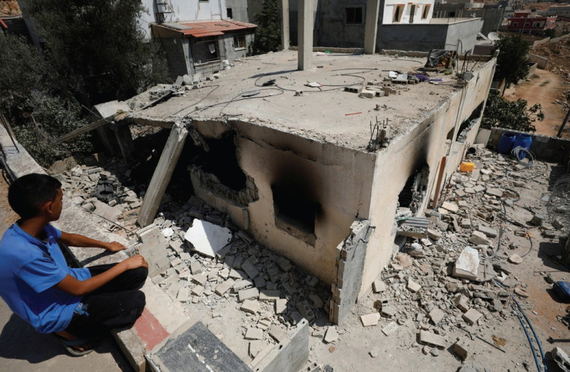 A boy looks at the family house of terrorist Adel Ankush in the village of Deir Abu-Mashal after it was demolished yesterday by the IDF using a controlled explosion.  (photo credit: MOHAMAD TOROKMAN/REUTERS)