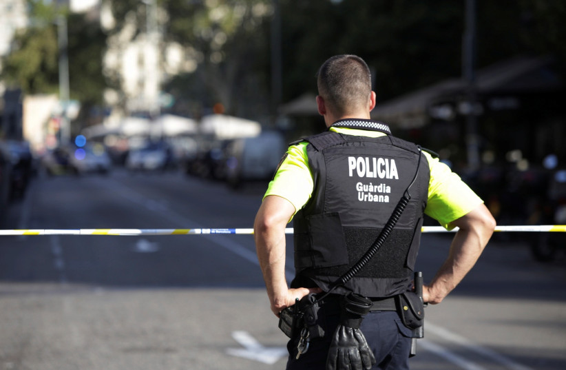 A Spanish police officer looks over a street in Barcelona after a van ramming attack there killed 13, August 18, 2017. (photo credit: REUTERS/STRINGER)