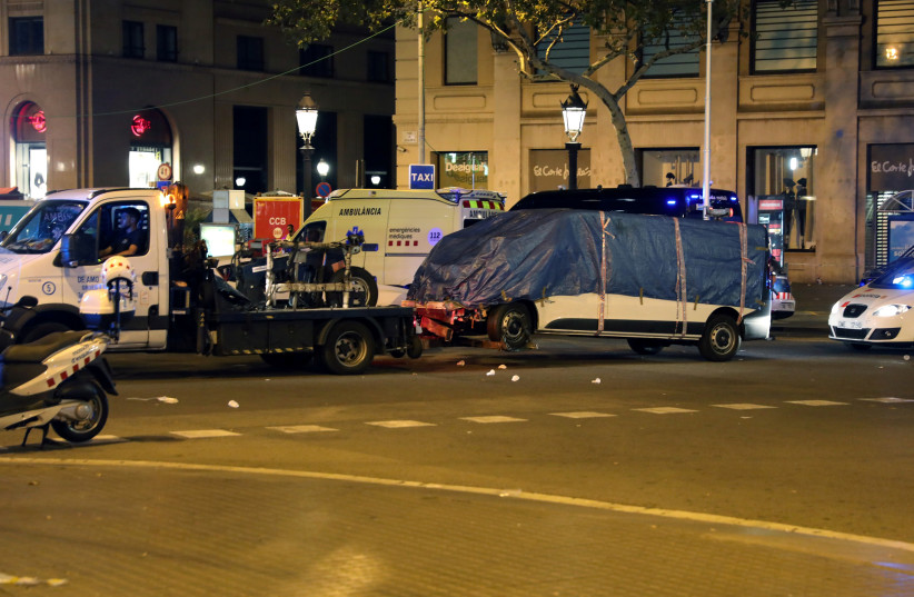 The suspected van is towed away from the area where it crashed into pedestrians at Las Ramblas in Barcelona, Spain, August 18, 2017. (photo credit: REUTERS/SERGIO PEREZ)