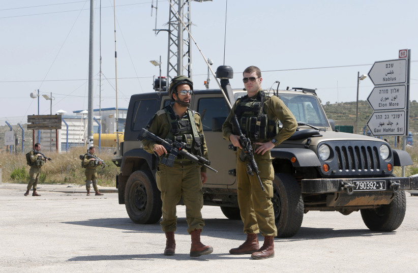 Israeli soldiers stand guard near the scene of an attack at Tapuach junction near the West Bank city of Nablus April 30, 2013 (photo credit: REUTERS)