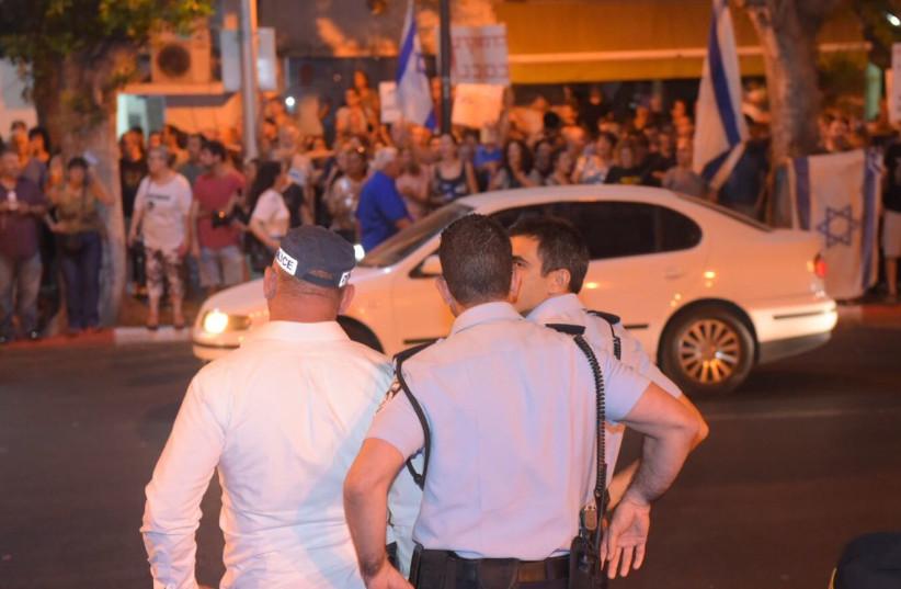 Israeli police watch protestors in Petah Tikva, August 19, 2017. (photo credit: AVSHALOM SASSONI/MAARIV)