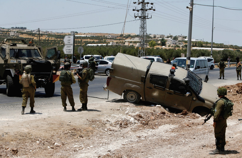 Soldiers stand guard at the scene of a car ramming and stabbing attack at the Tekoa checkpoint in the West Bank near Bethlehem in July. (photo credit: REUTERS)
