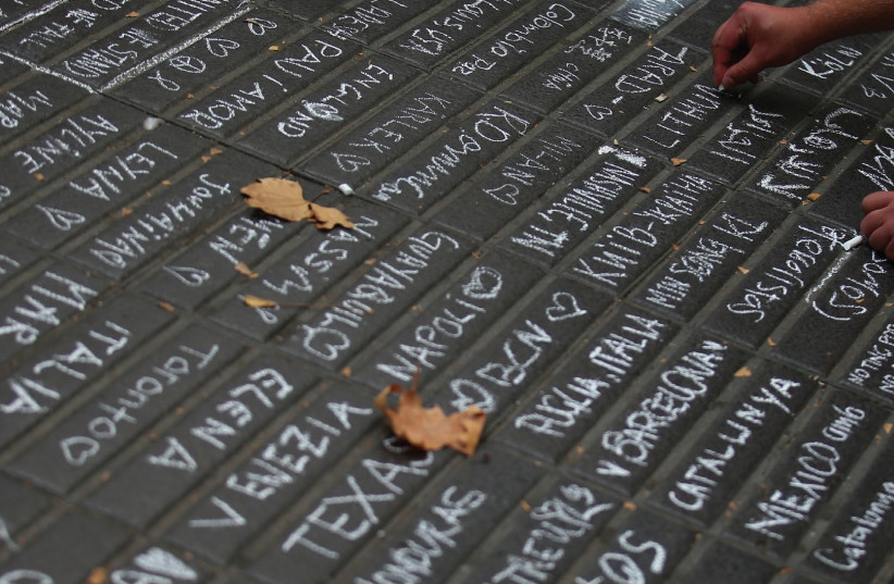A PERSON writes messages on a sidewalk at Las Ramblas in Barcelona on Saturday (photo credit: REUTERS)