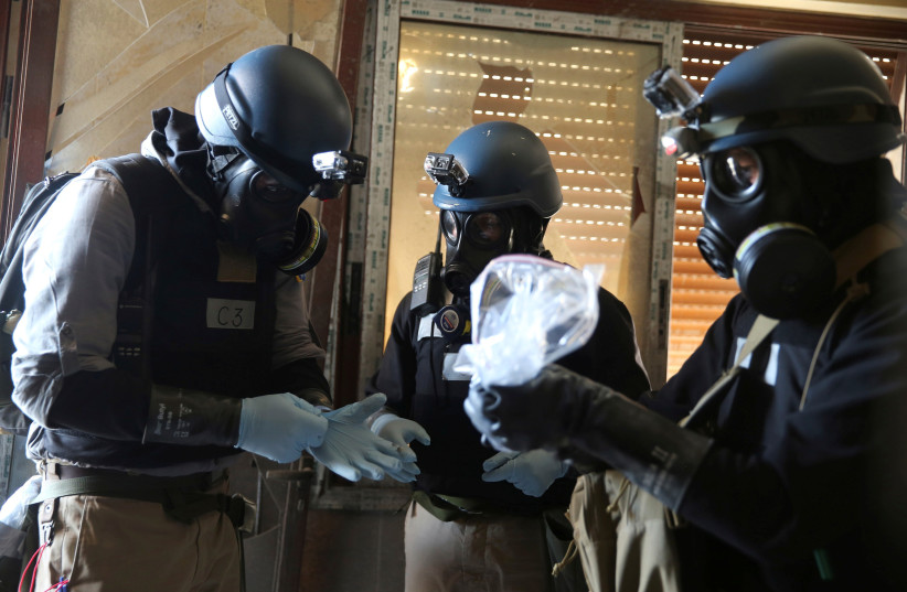A United Nations (U.N.) chemical weapons expert, wearing a gas mask, holds a plastic bag containing samples from one of the sites of an alleged chemical weapons attack in the Ain Tarma neighbourhood of Damascus, Syria August 29, 2013. (photo credit: REUTERS/MOHAMED ABDULLAH)